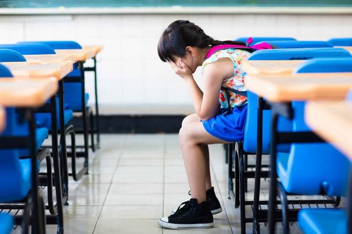 Little kid in a classroom with their hands covering their face.