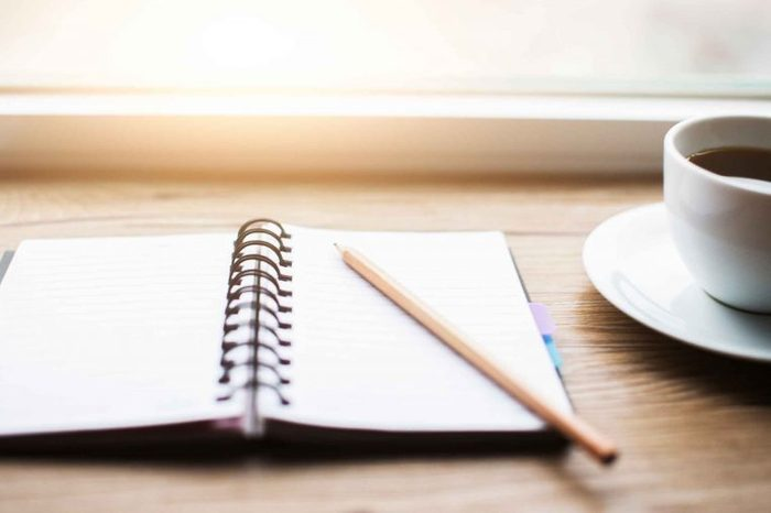 journal with pencil on a table next to a cup of coffee