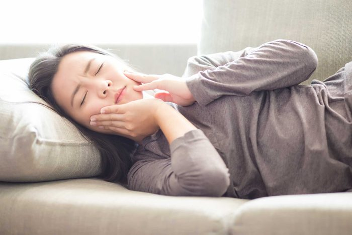 woman in pain lying down and holding her jaw