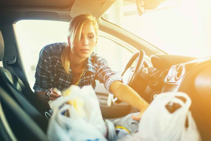 Woman taking groceries out of car