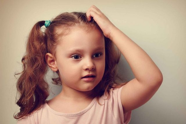Little girl with pigtails itching her scalp.