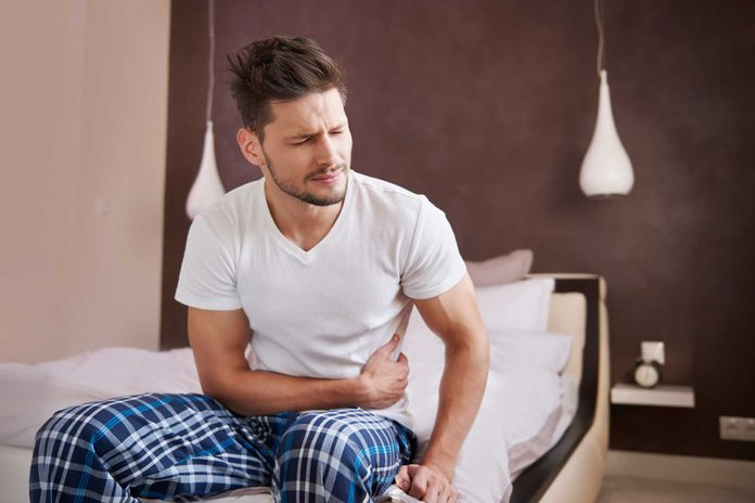 man in pajamas sitting on the edge of a bed and holding his stomach in pain