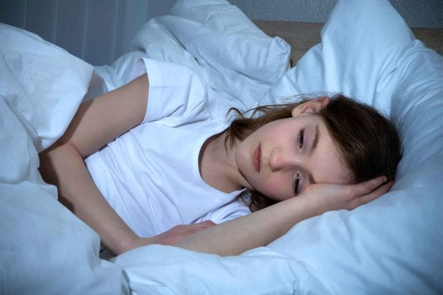 Little girl lying in white bed trying to sleep.