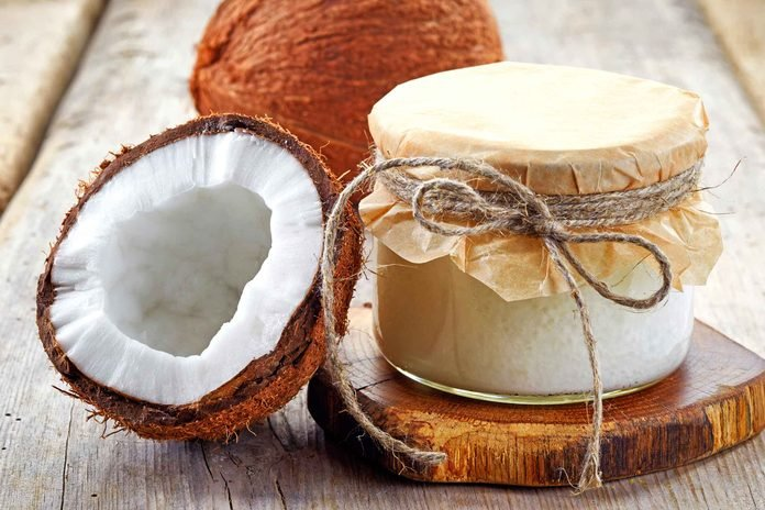 Container of coconut oil and raw coconut.
