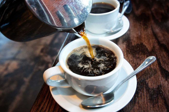 coffee pot pouring into a white cup and saucer