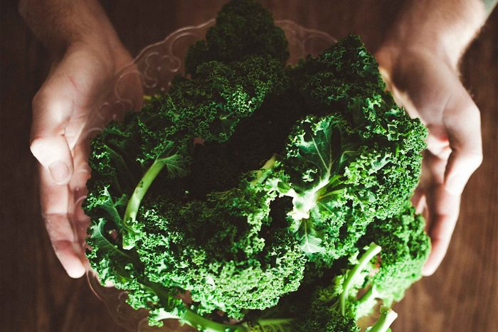 hands holding a bowl of leafy greens
