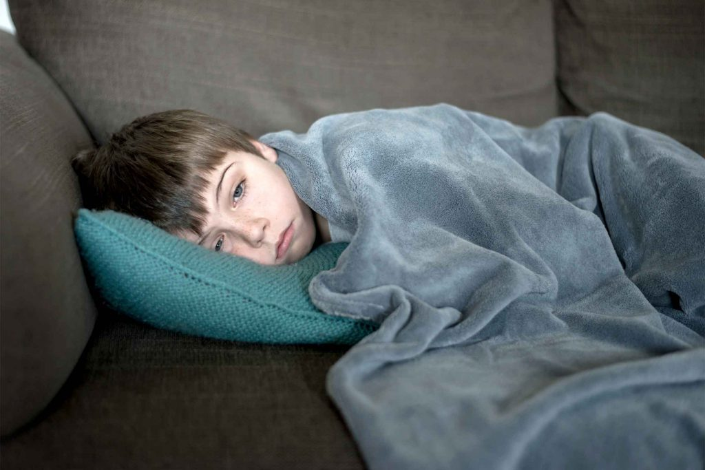 Sick child lying in bed with blanket
