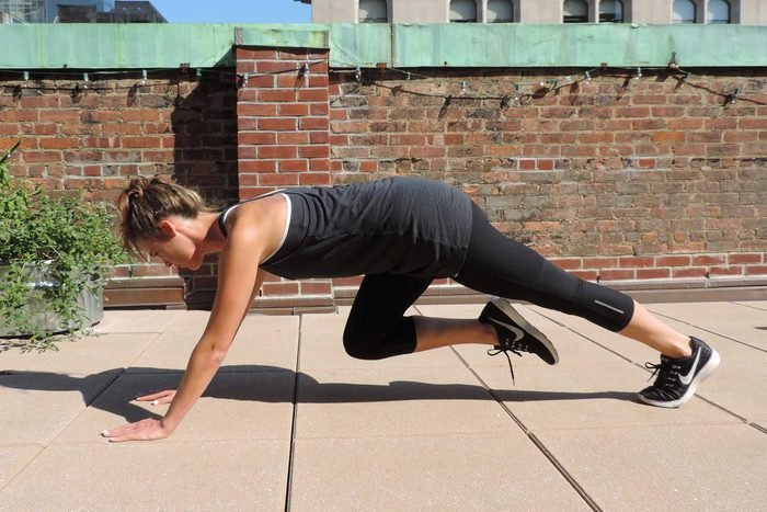 Woman in exercise gear doing mountain climber exercises.