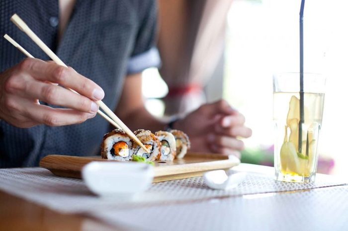 man eating sushi with chopsticks