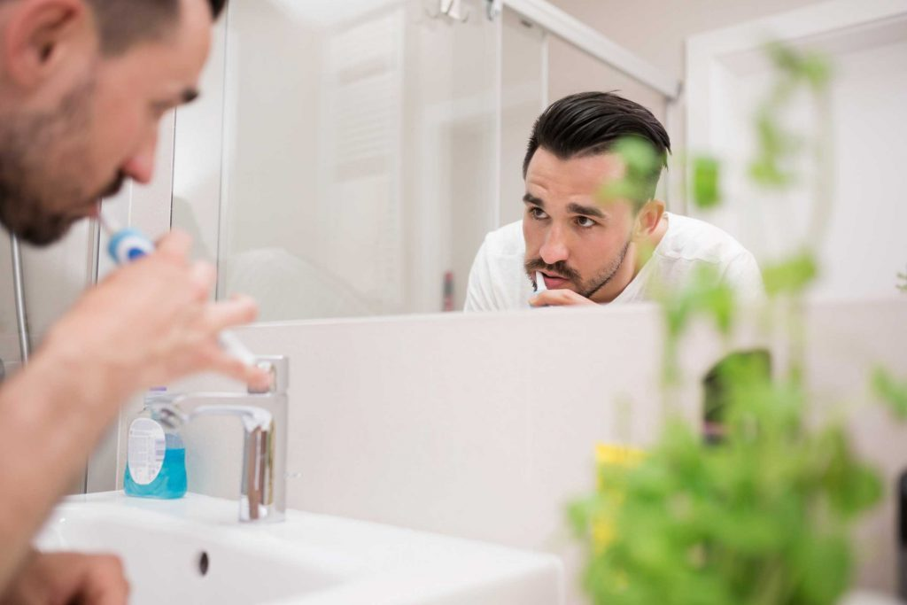 man brushing teeth and looking in mirror