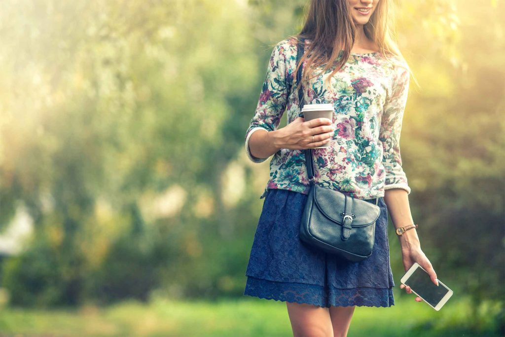 woman walking and holding a phone and a coffee cup