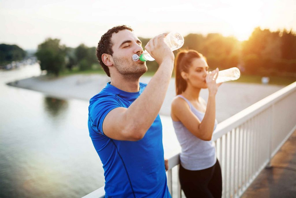 Exercising man and woman stop on a footbridge over a body of water to drink from their water bottles.