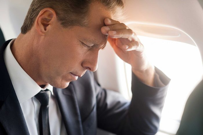 man in business suit on airplane with hand on head