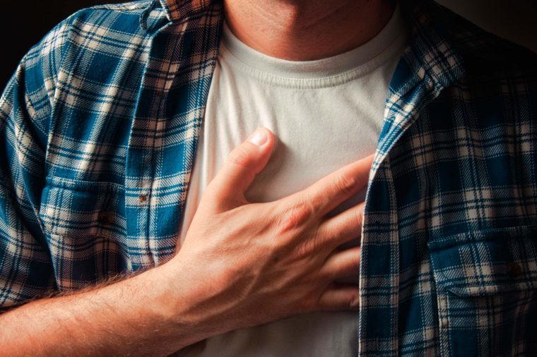 Man holding his heart as if having chest pain.