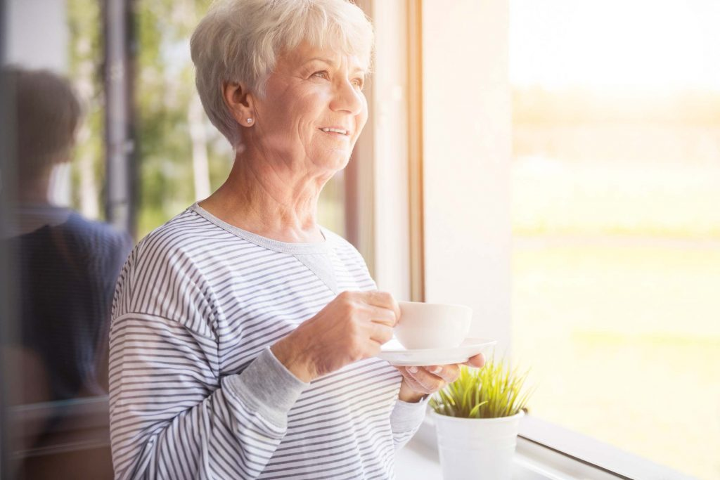 Smiling older woman enjoying a cup of tea while peering out a window.
