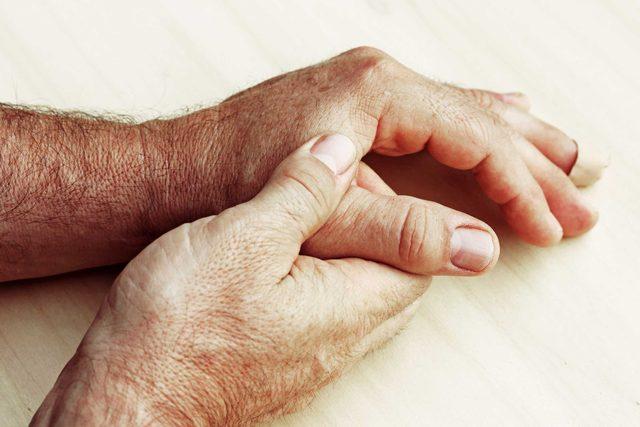 man massaging his thumb joint
