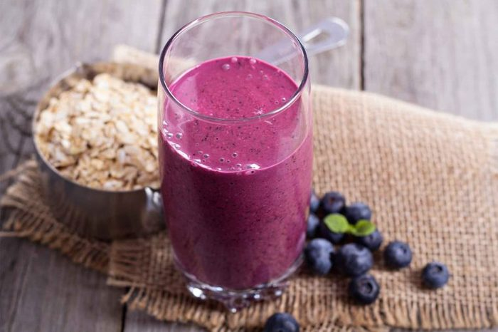purple smoothie next to berries and oats