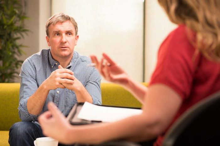 Man talking to a psychologist with a clipboard.