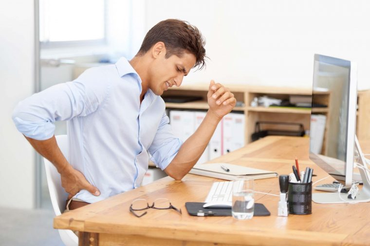 Man at a desk holding his back.