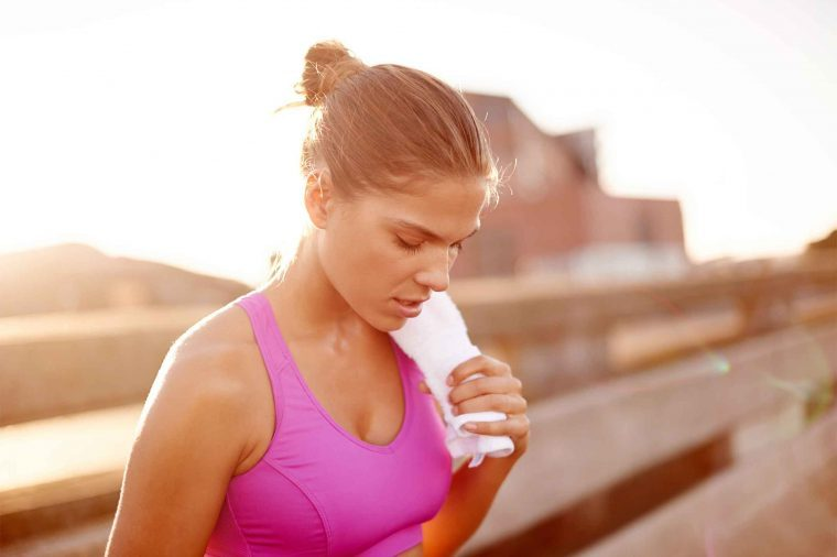 woman in exercise bra outdoors, breathing heavily