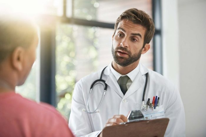 Doctor in a white coat and clipboard talking to a patient.