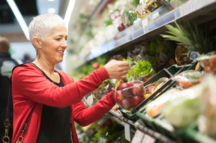 gray-haired woman shopping the produce aisle