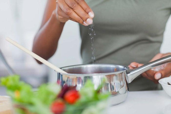 Woman sprinkling salt into a pot.