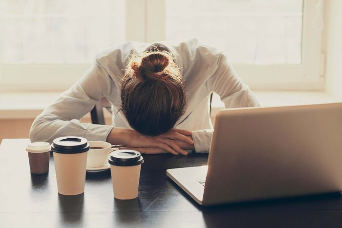 Woman at work with her head on her desk and surrounded by coffee cups.