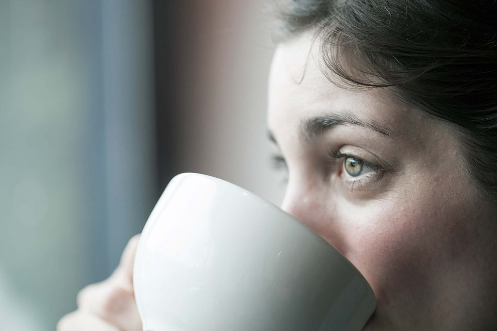 Woman with pale complexion sipping from a mug.