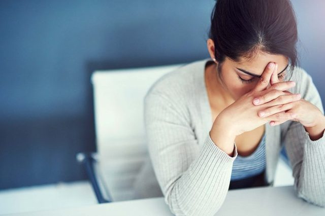 Tired woman resting her head on her hands at her desk.