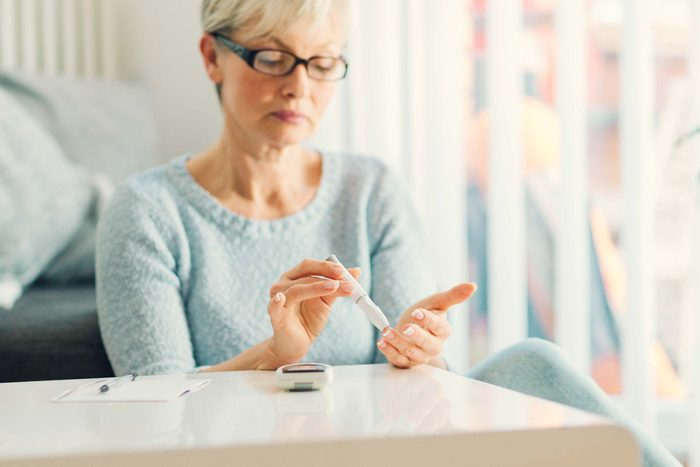 Middle-aged woman checking her blood glucose.