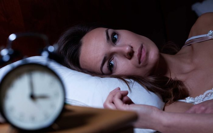 Woman looking at clock in bed