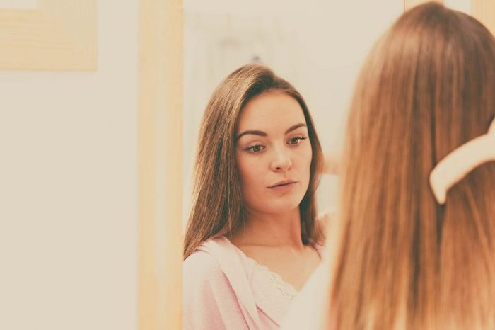 Woman combing her hair in the mirror.