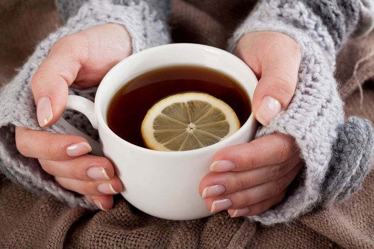 Woman in a sweater holding a cup of tea with a lemon slice.