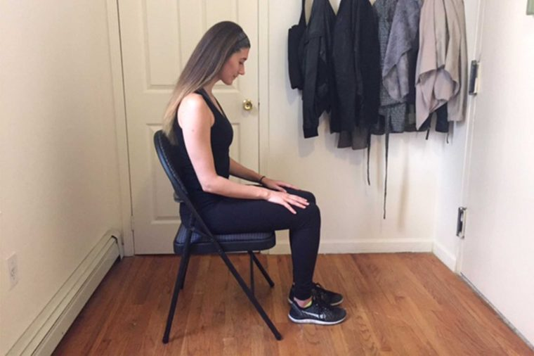 Woman in workout gear doing a seated exercise.