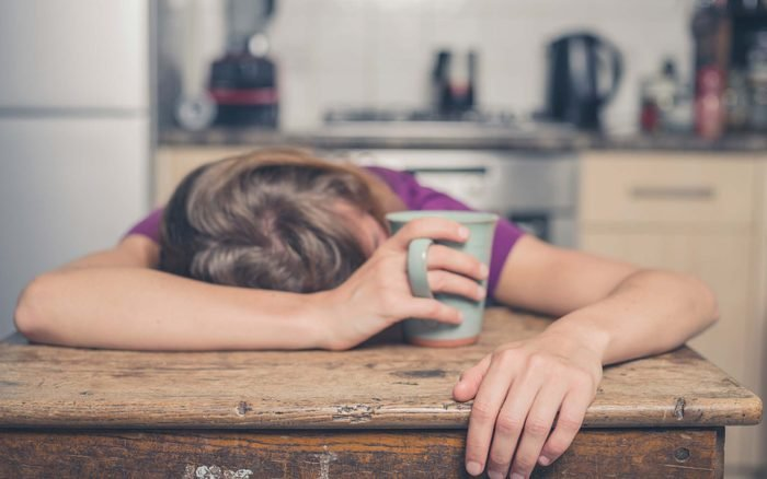 woman collapsed on a wooden kitchen table holding a mug