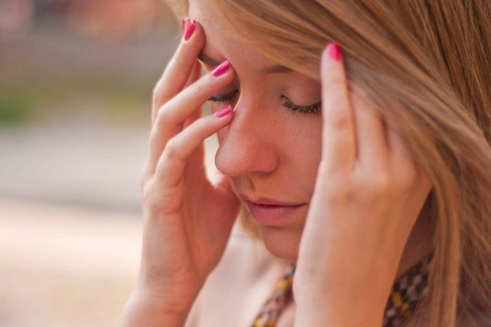 Woman with pink nailpolish holding her head as if tired.