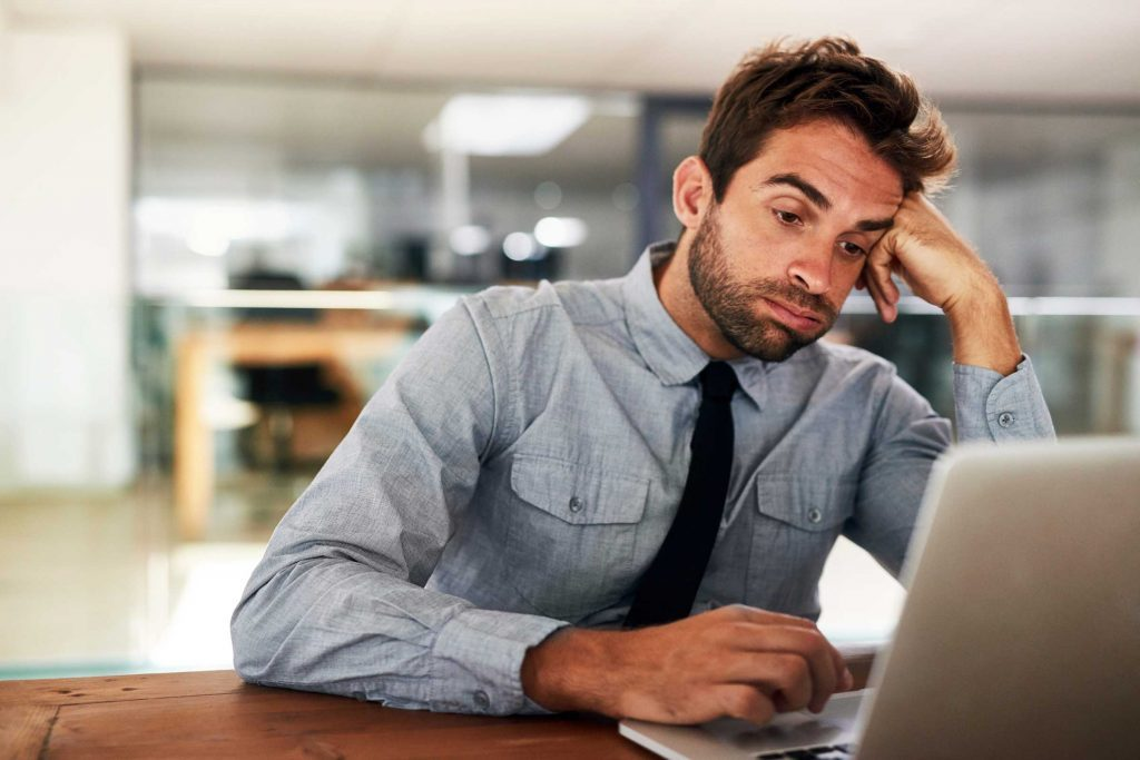 Man in front of computer, looking bored