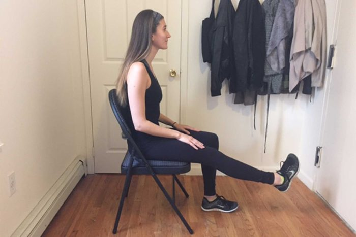 Woman doing seated ankle circle exercises.