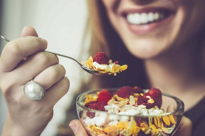 Woman eating yogurt with cereal and raspberries