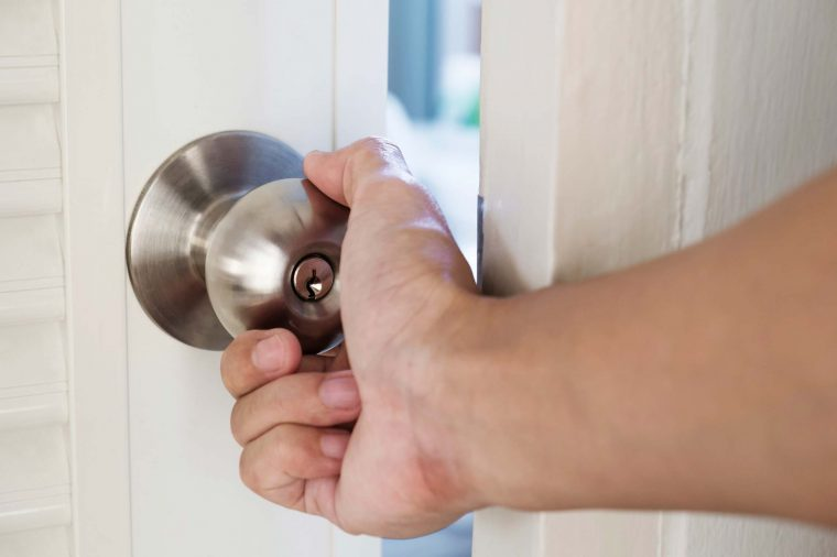 Person with their hand on a doorknob opening a door.