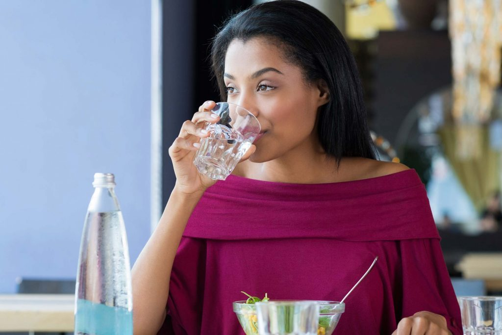 Woman drinking a glass of water at a restaurant.