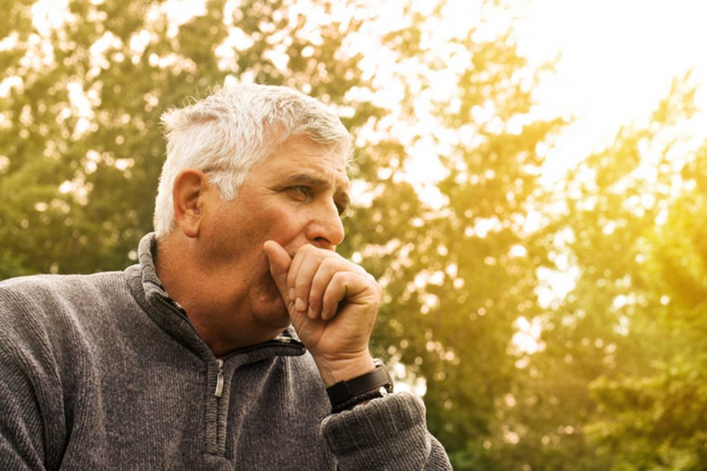 elderly man outdoors, coughing into his hand