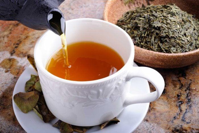 tea pot pouring into white mug and saucer next to bowl of tea leaves