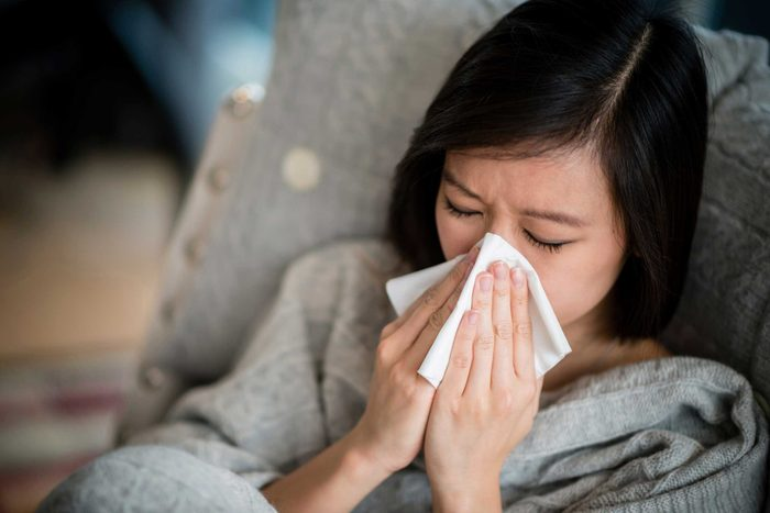 Asian woman sneezing into a tissue