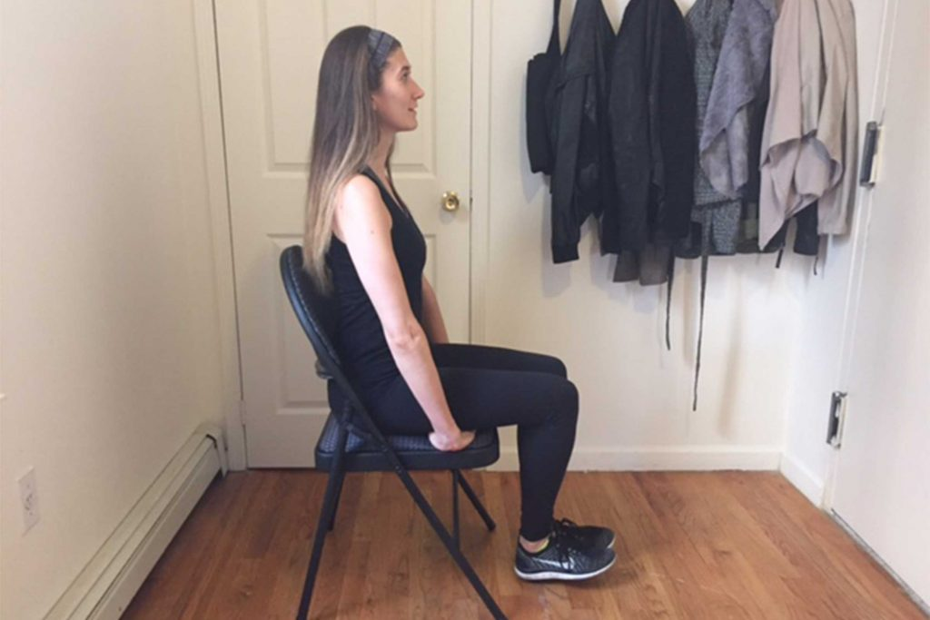 Woman doing seated knee lifts in a chair.