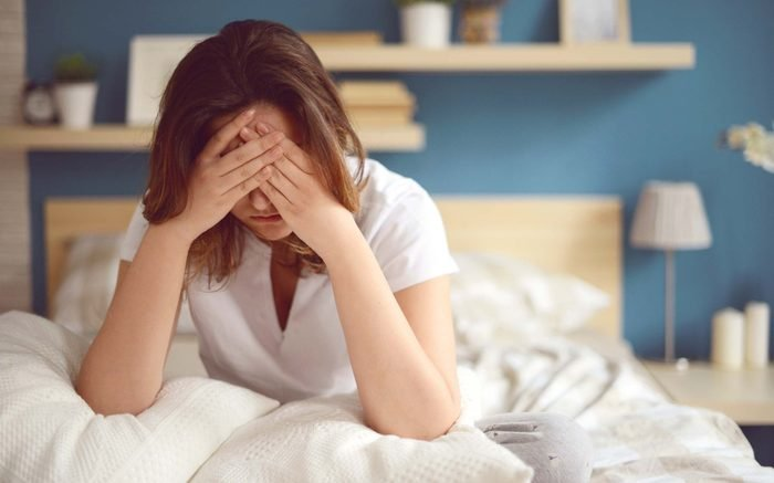 woman sitting in bed, holding head in hands and looking distressed