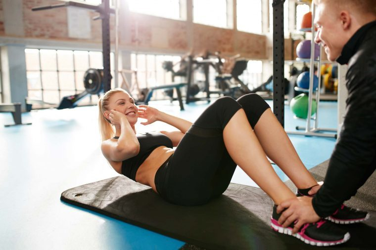 woman doing sit-ups with personal trainer