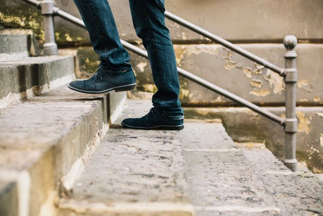 close up of just lower legs and feet of someone climbing the stairs