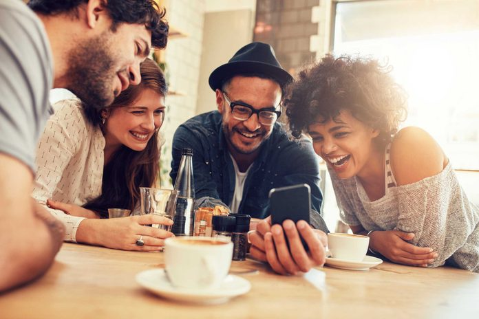 group of four people looking at smartphone and laughing